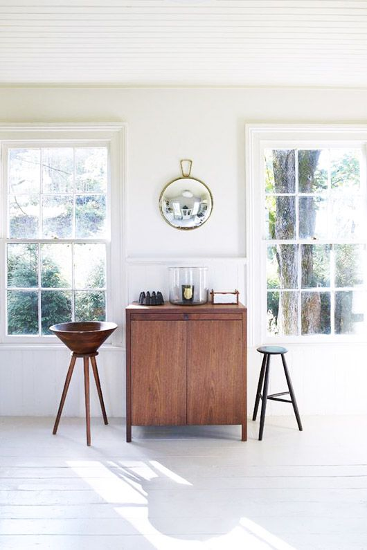 minimalist white living room with wood cabinet and circle mirror. / sfgirlbybay