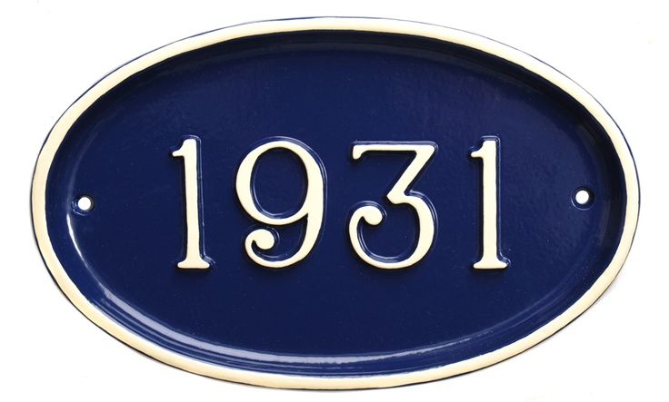 A very 1930's house number plaque in navy blue with a cream trim and numbers.