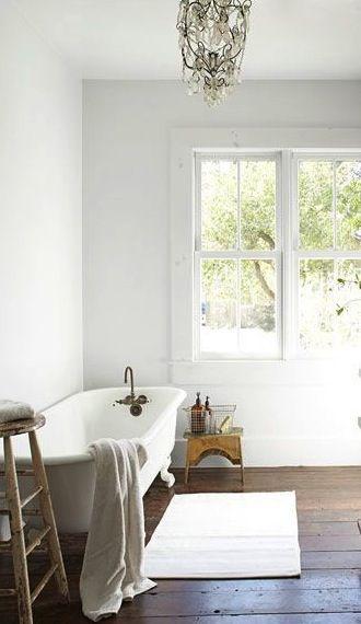 Rustic white bathroom // clawfoot tub // wood floors