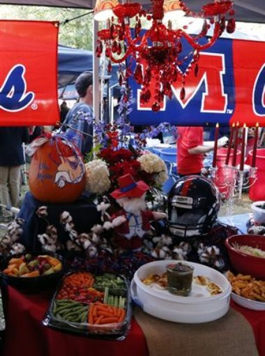 Elaborate food setups can be found in many of the tents as fans tailgate in The Grove at Ole Miss prior to an NCAA college football game against Alabama in Oxford, Miss., Saturday, Oct. 4, 2014. (AP Photo/Rogelio V. Solis)