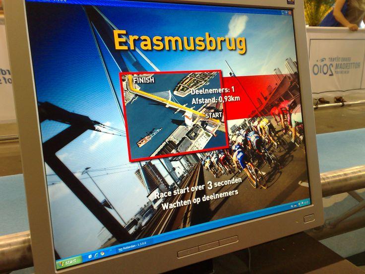 Op een racefiets, met de werkelijke weerstand de Erasmusbrug beklimmen.