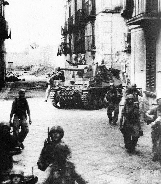 "https://flic.kr/p/D2Mcsb | 7,5 cm Pa.K. 40/2 auf Fahrgestell Pz.Kpfw. II (Sf.) ""Marder II"" (Sd.Kfz. 131) | Fallschirmjägern from Fallschirm-Panzerjäger-Abteilung 1, Kampfgruppe ""Gröschke"" (1. Fallschirmjäger-Division), marching in the streets of Barletta, Italy, 12 September 1943.  Picture and text courtesy World War 2 Photos  ________ The Panzer Pictures Database | @PanzerDB (Twitter) | panzerdb.com"