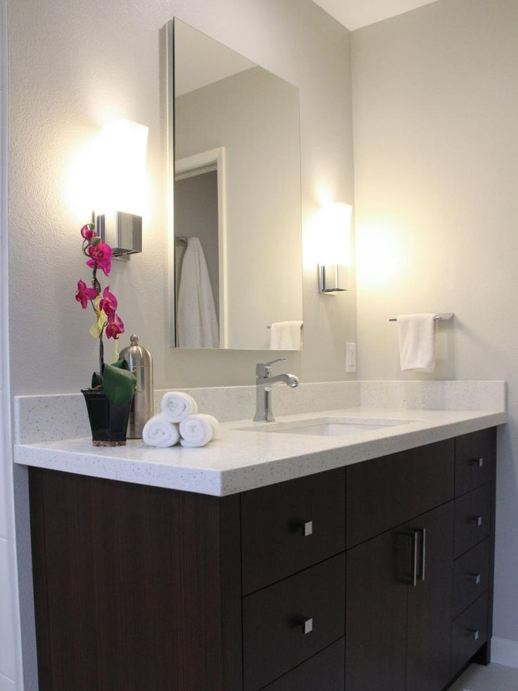Pic On HGTV presents a dark brown bath vanity with quartz countertop that features a mirrored medicine cabinet and sleek chrome wall sconces