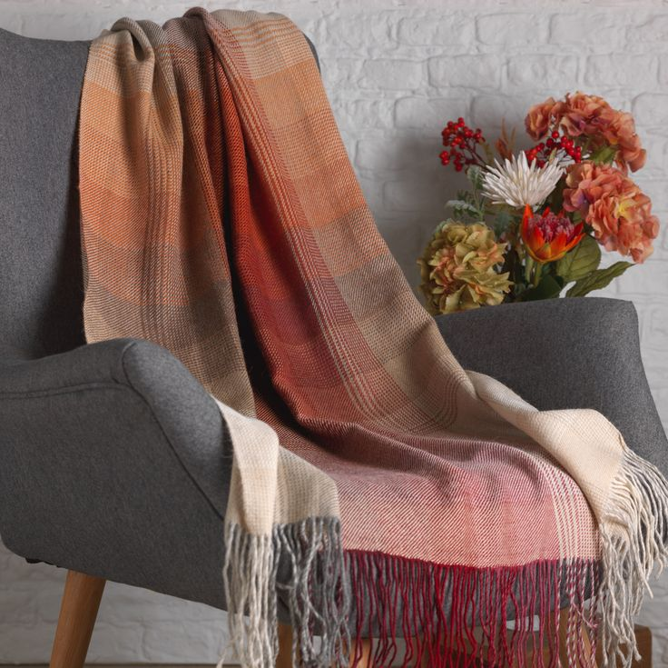 This handwoven luxury alpaca throw in warming tones has been crafted by traditional weavers in Peru. The colours blend together in a checked square design, and either end has a twisted feature fringe.