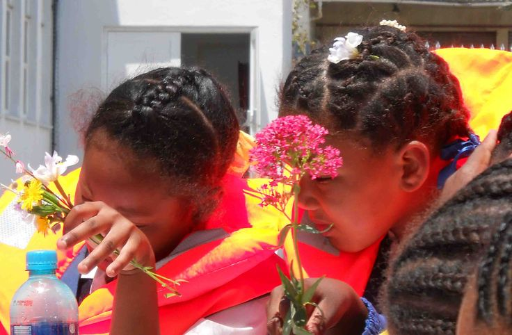 Children appreciating the beauty of flowers.