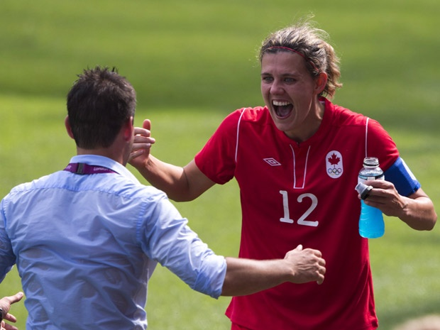 Christine Sinclair, captain of the Canadian soccer team, is congratulated by her coach John Herdman.