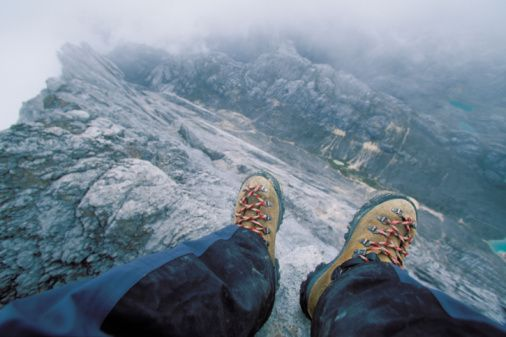 Stock Photo : High angle view of boots on a cliff edge.