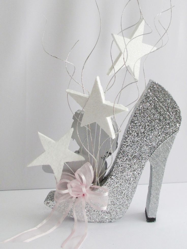 This adorable unique baby centerpiece was created to resemble the customers baby shower invitation. We created the high heeled shoe out of Styrofoam, painted and glittered, and added some faux rhin...