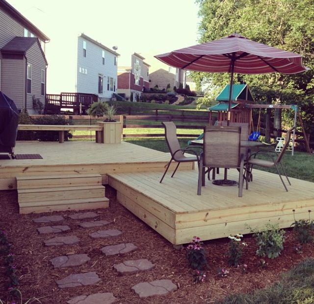 Two Level Ground Level Deck Including A Bench With Extra Seating And  Planters On Either Side