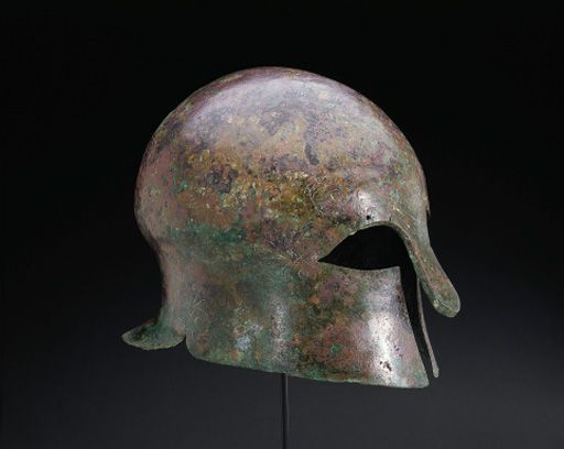 A GREEK BRONZE CORINTHIAN HELMET   circa late 6th century b.c.   Of hammered sheet, rounded in form with a domed crown, a flaring neck guard, long nose guard and finely cut eyes reinforced on the underside, a perforation above each eye, with incised palmettes at the outer corner of each eye and at the perimeter where the neck guard meets the cheek guard, a palmette rising between the eyes at a V formed from the bodies of two snakes, their heads raised and facing each other with open mouths,