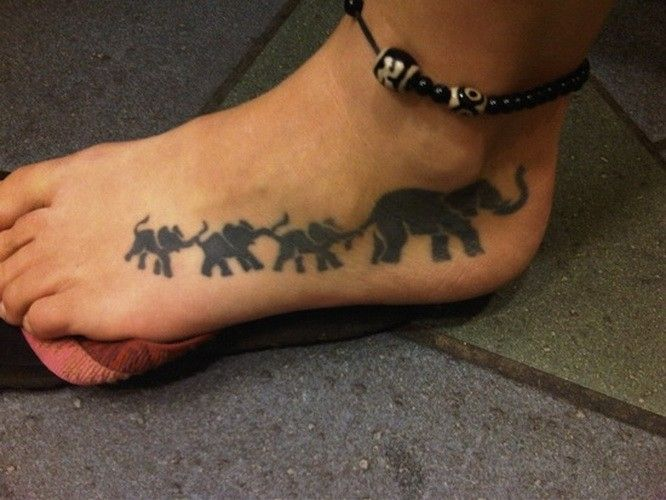 Cool black-colored elephant family tattoo on foot
