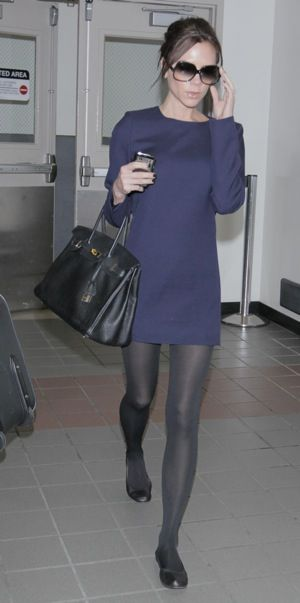 Victoria Beckham Wearing a Navy Dress with grey tights, black shoes and bag