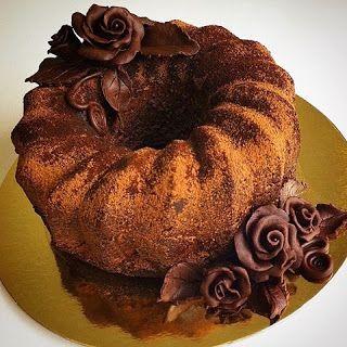 A foto mostra um bolo de chocolate redondo, alto em forma de gomos, salpicado por cacau em pó. Sobreposto à esquerda, na superfície, um arranjo em formato de uma rosa cercada por folhas também de chocolate. Na diagonal, sobre a base de papelão dourado e redondo, outro arranjo floral maior, no mesmo estilo com três rosas.