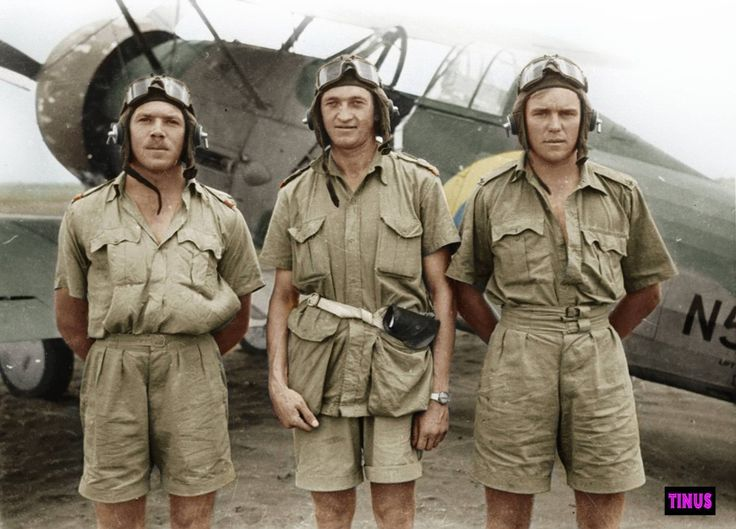 """No. 2 Squadron pilots in East Africa 1940-'41 (Gladiator aircraft in the back ground). From left to right: Lt. Pieter Fritz, Lt. Adrian """"Coley"""" Colenbrander, Lt. Basil Guest. Only Guest will survive the war. Colenbrander was a popular member of the squadron and was shot down and killed in 1942 just after the Alamein break-through as 2 squadron's OC.  Photograph from SAAF museum."""