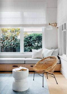 woven circular chair, cement side table, grey rug, built in bench daybed, accordion sconce, white blinds