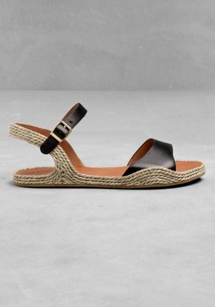 flat sandals w/ natural rope covering the sides and heel strap, and black leather straps on the ankle and toe.