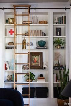 White bookshelf with rolling ladder.