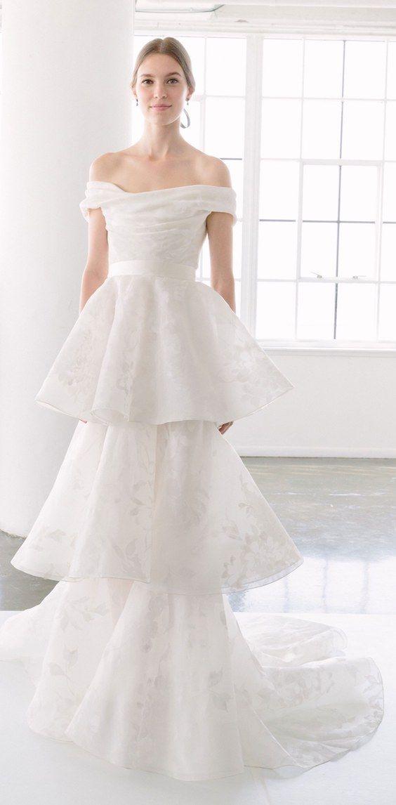 Una interpretación moderna y romántica del vestido de novia tipo columna con un delicado escote palabra de honor con falda en capas de Marchesa 2018.