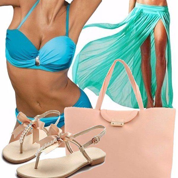 Un look da spiaggia, ma in versione chic da indossare per un apericena a bordo piscina composto da bikini bicolore con fasce che si incrociano, gonna pareo color acquamarina, sandali bassi color cipria con fiocchetto in raso e perle e borsa Blumarine color cipria.
