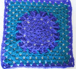 The Amethyst Square is accented with teal colored yarn. Learn how to crochet granny squares in these vibrant colors and you'll never want to stop making them.