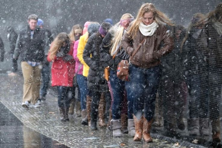 Tourists seek shelter from the falling snow by walking close to the Vietnam Veterans Memorial in Washington on Jan. 21, 2014.