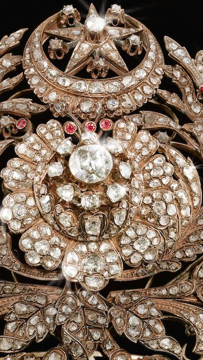 {DETAIL} A RARE OTTOMAN DIAMOND AND RUBY SET GOLD TIARA, TURKEY, CIRCA 1800 the foliate openwork frame supporting attached elements set with cut-diamonds, the centre with a large diamond floral rosette radiating diamond-set petals issuing floral sprays set with diamonds and rubies, the crown with a star and crescent motif, suspension loops to the sides