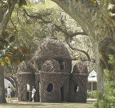 Outdoor environmental sculpture made of tree saplings shaped like a desert dwelling