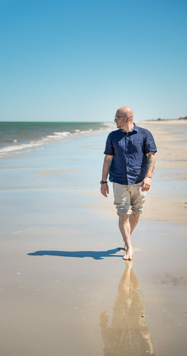 Tony, a bald man walking on the beach in adelaide Henley or grange 2016 reflecting at the ocean