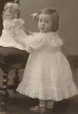 Antique photo of a sweet little girl with her doll, circa 1900.