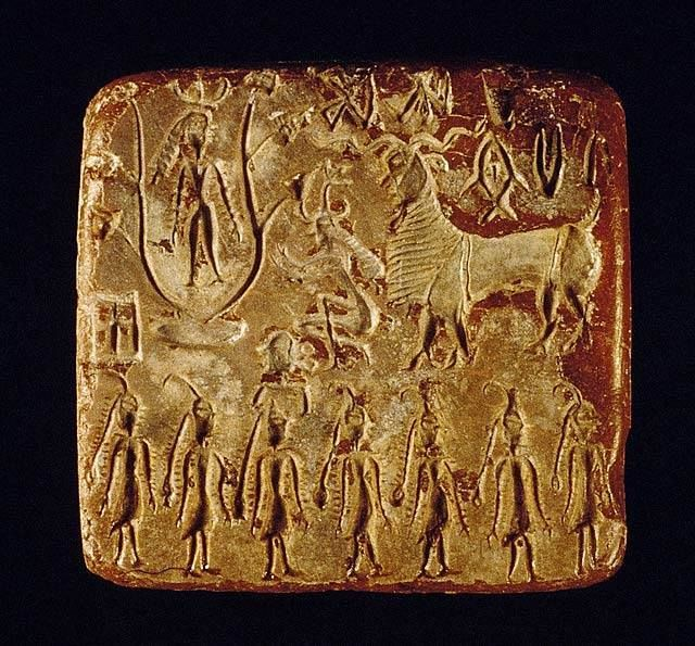 """One of the most evocative seals from Mohenjo-daro, depicting a deity with horned headdress and bangles on both arms, standing in a pipal (sacred fig) tree and looking down on a kneeling worshiper. A human head rests on a small stool and giant ram and seven figures in procession complete the narrative. Asko Parpola writes """"An anthropomorphic figure has knelt in front of a fig tree, with hands raised in respectful salutation, prayer or worship.  Or?  Astrology?  BRS"""
