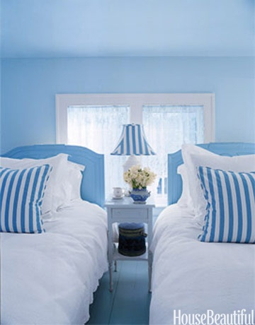 Designer Valerie Smith used antique oversized twin beds for this guest bedroom. The blue and white palette creates a crisp and simple look. Featured in the March 2006 issue.