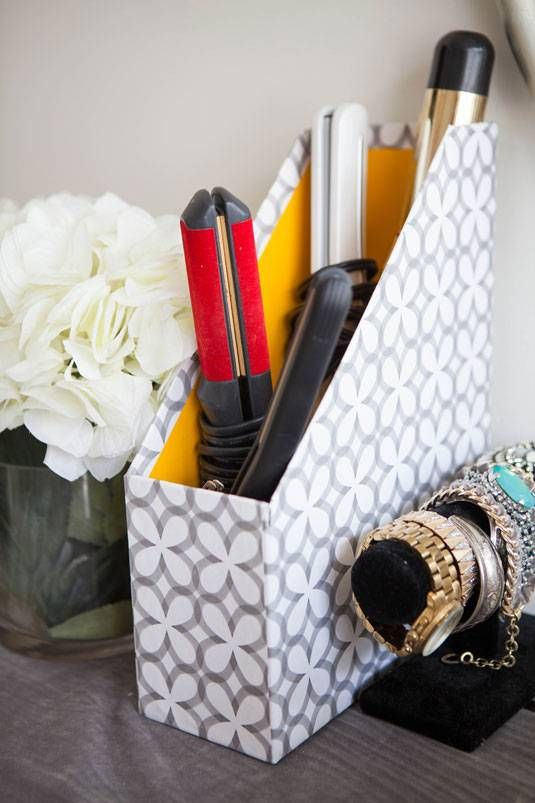 20+ Creative Uses for Magazine Holders to Organize Your Home --> Store your flat or curling iron and other hot tools inside a decorative magazine holder