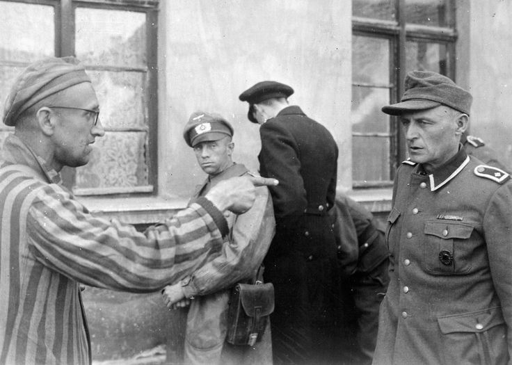 Former Russian prisoner liberated by US 3rd Armored Division pointing out former Nazi guard who brutally beat prisoners, possibly at Mittelbau-Dora Concentration Camp, Nordhausen, Germany, 14 May 1945.