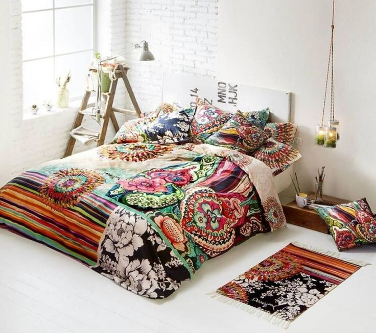 chambre à coucher blanche de style hippie chic avec une literie à motifs multicolores, tapis rustique bariolé et suspensions originales
