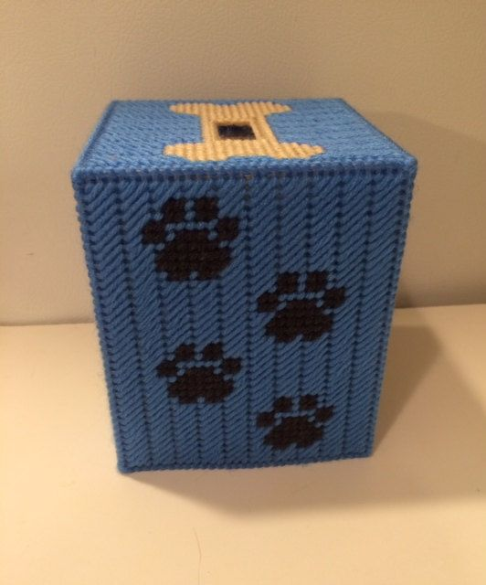The Maidens sure do love our pets and we know you do too. Why not have a box made that looks like your pet! You can customize it with paw prints or bones or something sentimental. This box features a beige Pug on the front and back of the box. The alternating sides of the box cover have paw prints. The top of the box has a bone right in place where the tissues can be pulled out. Pricing is per 1 boutique size tissue box cover.  Our tissue box covers are perfect for bathroom decor, offices…