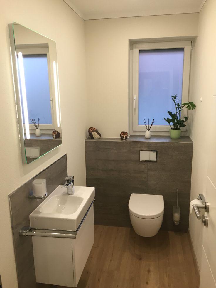Gäste-WC teilgefliest mit grauen Fliesen in Betonoptik und Designboden in Holzoptik