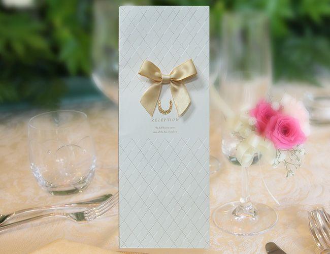 【リュバン(ホワイト)席次表A3】ホワイトカラーの冊子に大胆に飾られたイエローゴールドのリボンが印象的なデザインの、「リュバン(ホワイト)A3」席次表。「リュバン」とは、フランス語で「リボン」の意味。