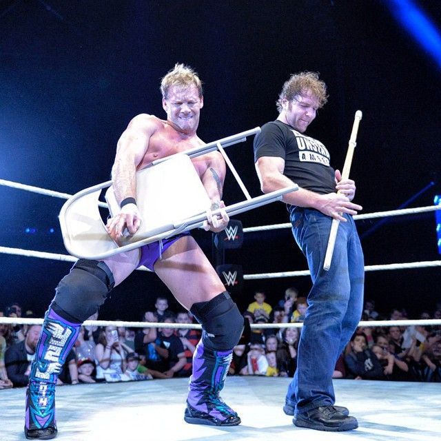 WWE Superstars Dean Ambrose and Chris Jericho playing air guitar at a WWE live event in Glasgow