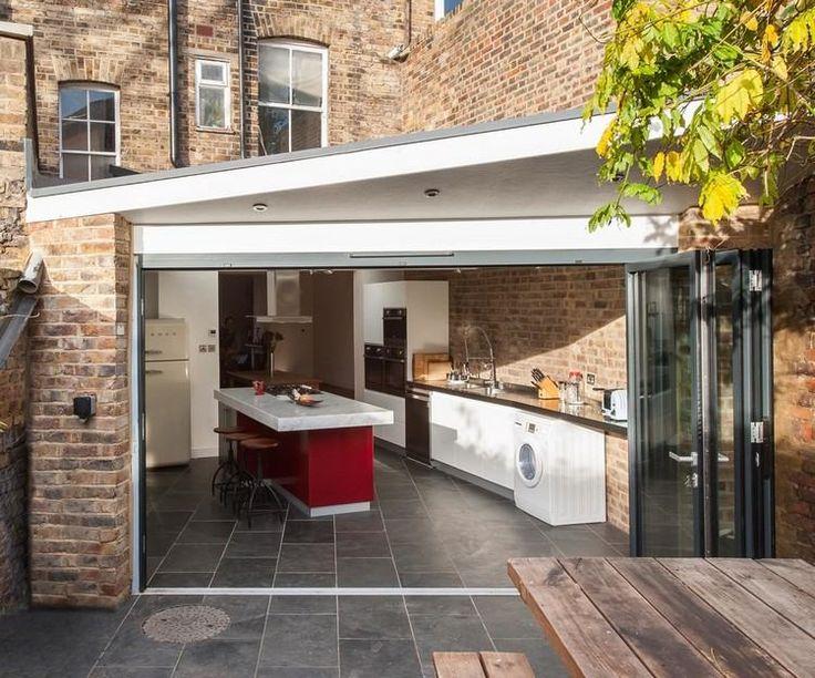 extension de maison aménagée en cuisine extérieure avec meubles design et carrelage sol gris anthracite