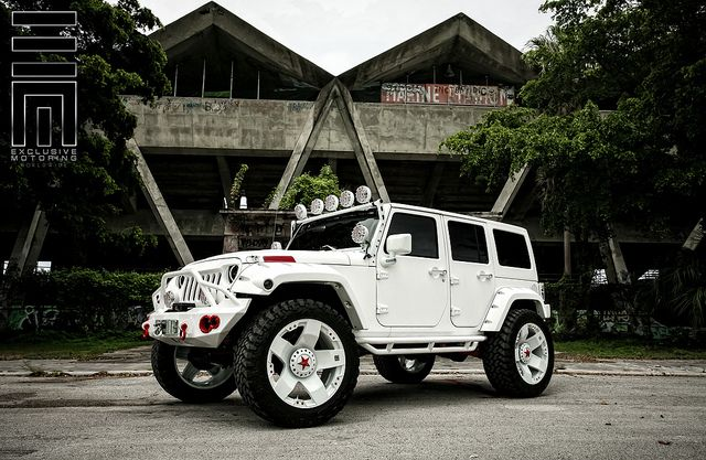 """Jeep Wrangler with complete white carbon fiber wrap, custom LED side steps, Magnaflow exhaust, lifted on 24"""" XD Rockstar wheels, with a complete custom Focal and JL Audio sound system."""