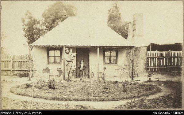 Man with two children outside a rendered cottage with corrugated iron roof, small formal garden and paling fence, Hill End, New South Wales...