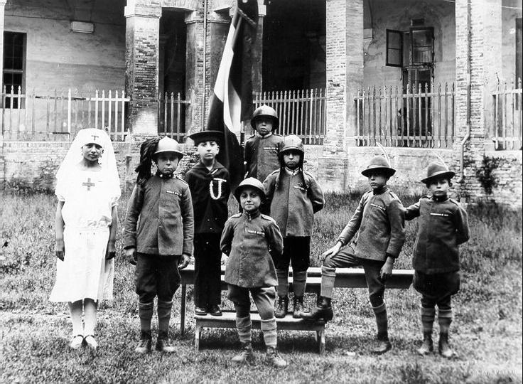 Durante una festa scolastica un gruppo di allievi posa con uniformi militari.  1930 /At a party school students posing with a group of military uniforms.