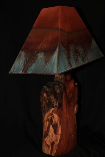 Mesquite is from the trees typically found growing in the Southwest and the shade is made from copper with a feather motif.  The lamp base is made from the burl wood of the mesquite tree, typically found in the Southwestern region of the United Sates. The shade is hand crafted copper created by New Mexico artist, W. Kohler