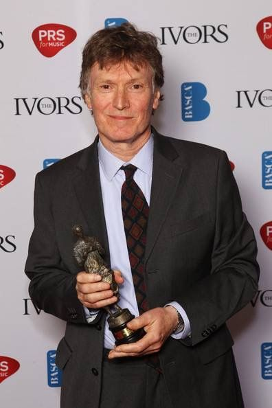 Steve Winwood holding the Ivor Novello Award he won in 2011 for Outstanding Song Collection. The award is given to honor excellence in music writing.
