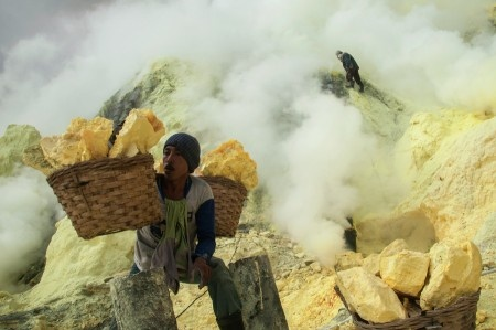 Anggi Anggoman: A miner carries 70 to 120 kilos sulfur in a 3-km-trip. They got paid 780 rupiahs for each kilo. (Mount Ijen, Banyuwangi, East Java, Indonesia).