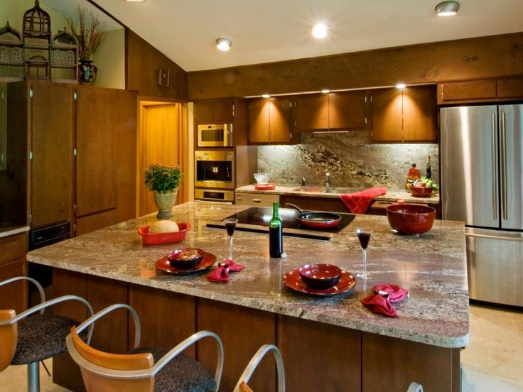 This kitchen boasts a large granite-topped island as well as a granite backsplash and countertops. The wood cabinets are complemented by stainless steel appliances and accented with red dinner decor.