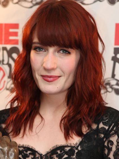 Florence Welch wavy shoulder-length hairstyle with straight, blunt bangs and cherry red lipstick | allure.com