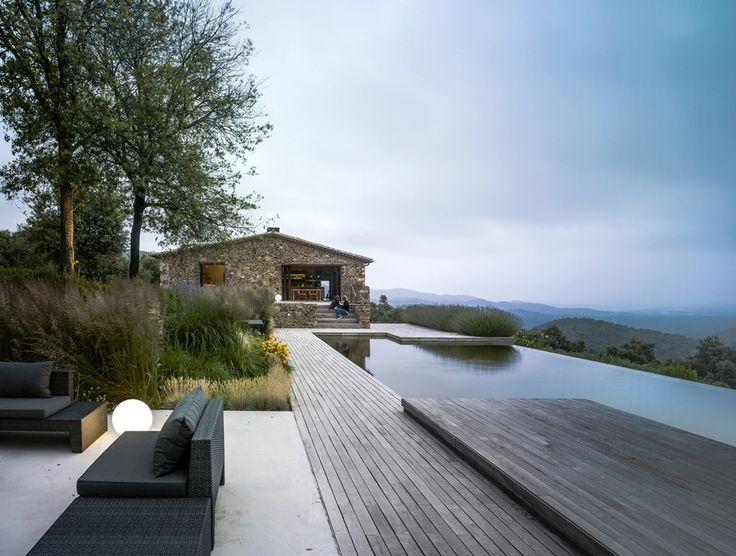 O projeto aproveitou a estrutura de pedra de uma antiga casa de fazenda catalã para criar uma nova casa aconchegante e super integrada com a natureza.
