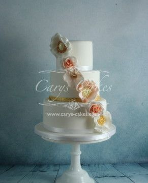 3 tier wedding vintage wedding cake, decorated with peach and gold flowers with the additional brooch.