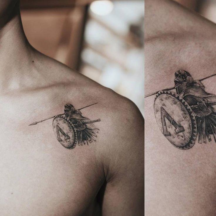 Single needle Spartan tattoo on the left shoulder.